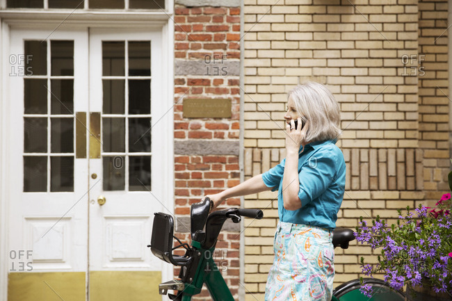 A woman walks her shared bike down a city street while talking on the phone