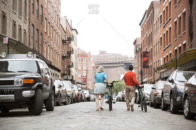 A couple walks their shared bikes down a city street