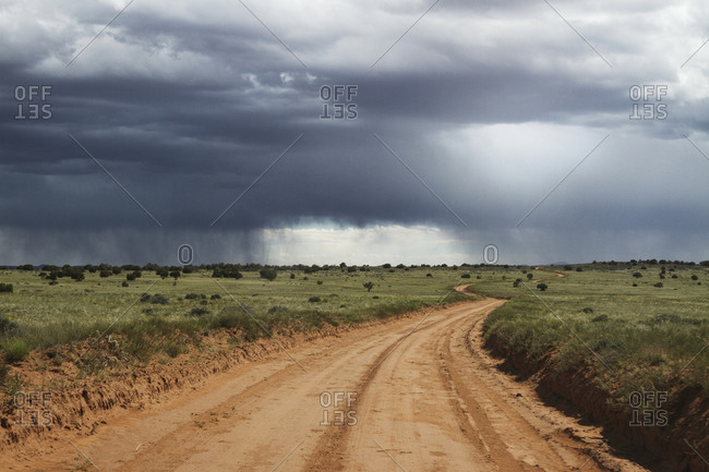 Rainstorm in the distance over a dirt road in Texas