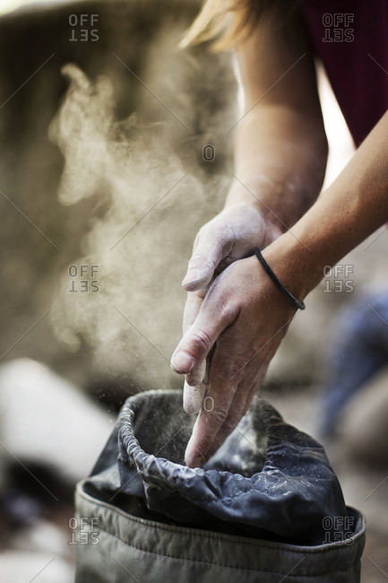 Close up of a rock climber using a chalk bag