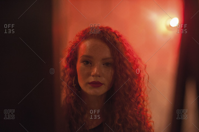Young woman bathed in red light
