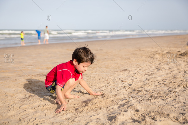 2f41cc778 Young boy in t-shirt and shorts digging in sand stock photo - OFFSET