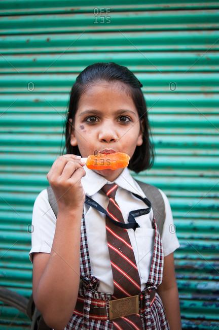 Varanasi, India - April 9, 2013: A schoolgirl eats a popsicle