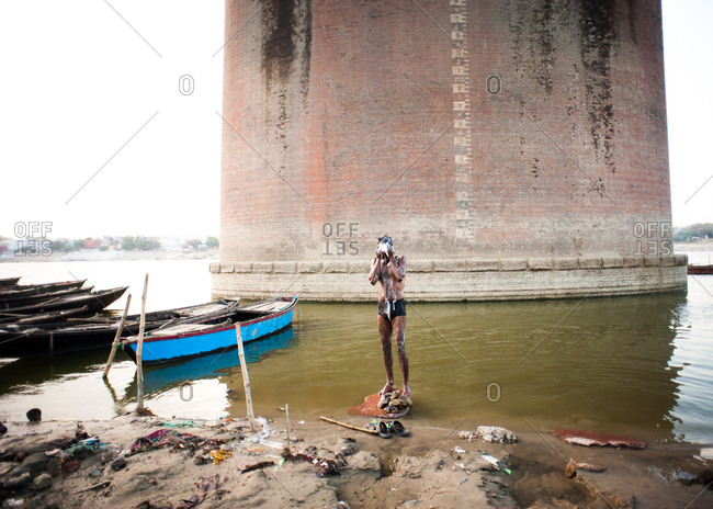 A man washes at the riverbank