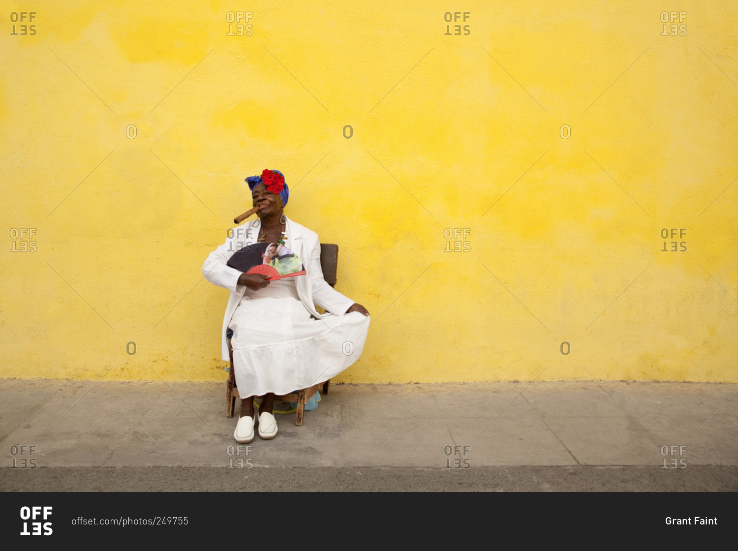 Cuban woman in white dress with fan smoking a cigar against bright ...