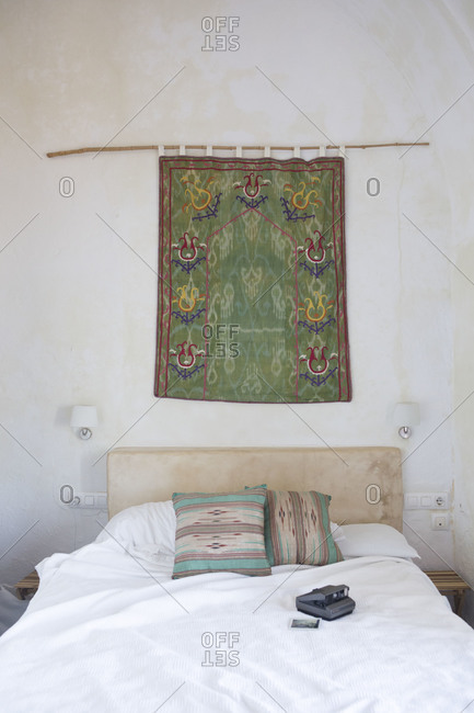 Tapestry hanging over a made bed