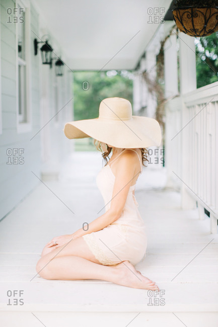 Woman wears a summer hat on a porch