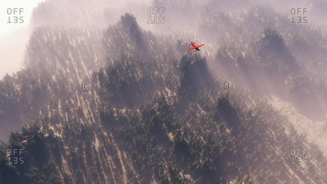 Red float plane flying above a misty forest landscape
