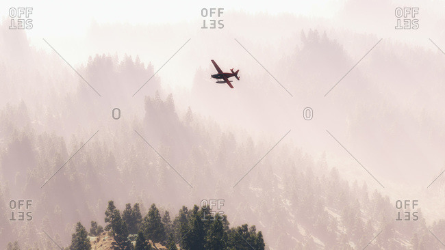 Float plane flying above foggy mountain wilderness