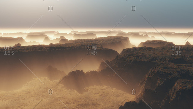 Light shining through landscape of misty canyons and plateaus