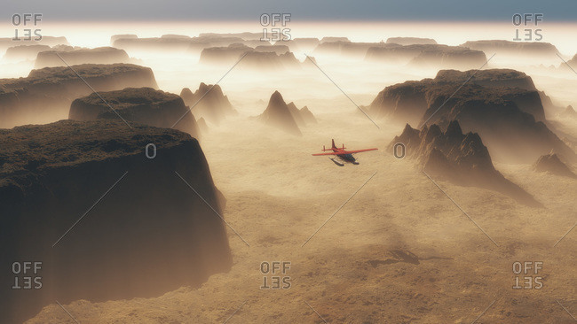 Red float plane flying through rocky landscape of buttes and mountains