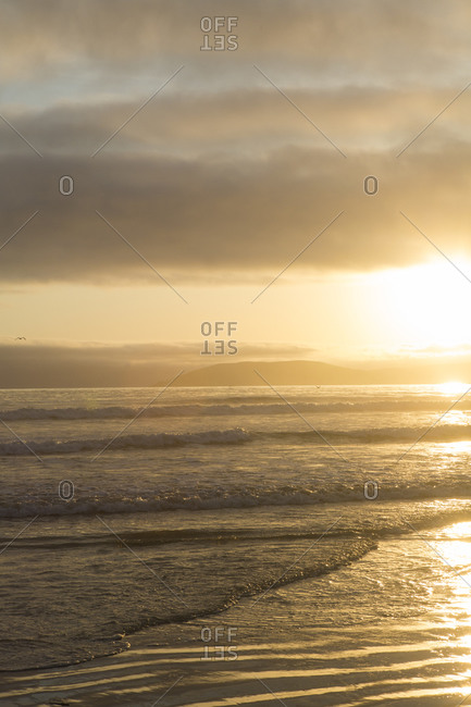 Gentle waves roll onto beach at sunset