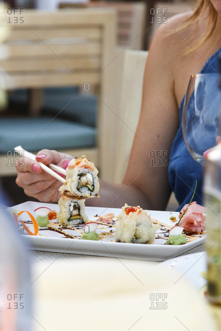 A woman eats sushi - Offset