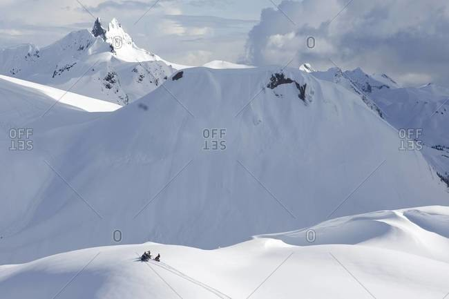 Skiers head up a mountain on snowmobiles in Whistler, Canada