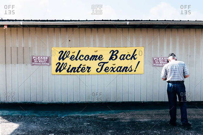 Man standing in front of a welcome sign on a building in Texas