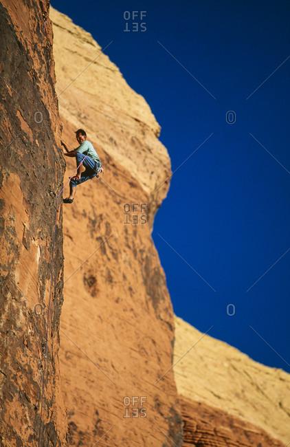 Rock climber ascending a steep cliff
