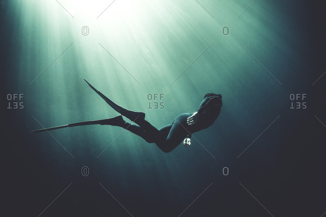 Scuba diver and sunrays in dark waters
