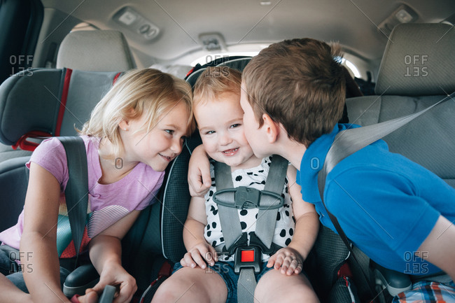 Affectionate siblings kiss their toddler sibling in the back seat of a car