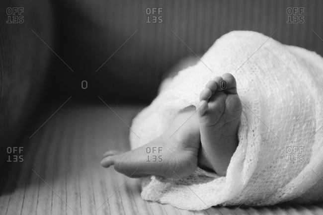 Feet of a swaddled newborn baby lying on sofa