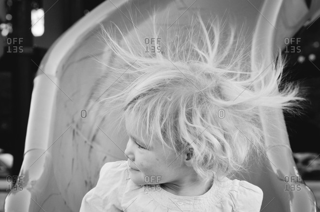 Little girl on slide with hair electrified with static electricity