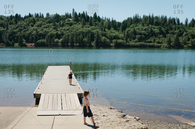 Boy and girl walking on a lakefront dock