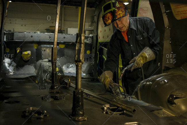 July 18, 2014: A welder working on the armored flooring of a client's SUV