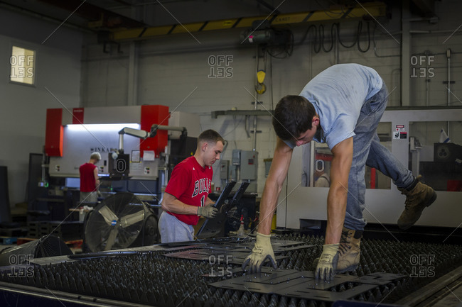 July 18, 2014: Workers remove pieces of cut metal from a state-of-the-art laser steel cutter in a armored vehicle factory