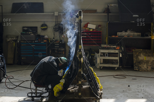 July 18, 2014: A welder welds armor plating to the inside of a vehicle's doors