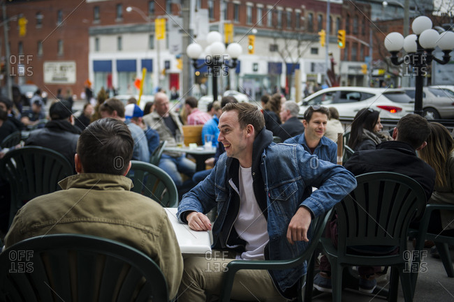 April 12, 2014: A crowd of patrons enjoy an outdoor  patio of a restaurant in downtown Toronto during a chilly spring day