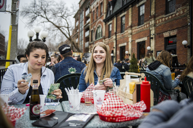April 12, 2014: Two women settle their tab at an outdoor  patio of a restaurant in downtown Toronto