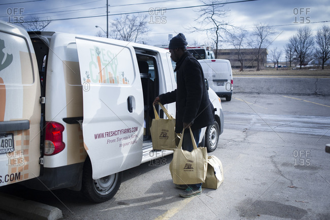 April 2, 2014: A volunteer packs food into a van for distribution  at an urban farm in Toronto, Canada