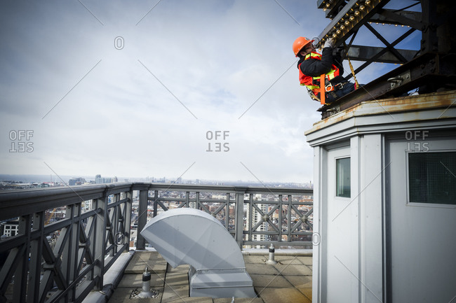February 25, 2014: A worker changing light bulbs on the Canada Life Insurance building in downtown Toronto