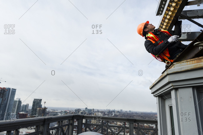 February 25, 2014: A worker changing light bulbs on the Canada Life Insurance building in downtown Toronto, Canada