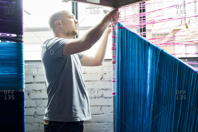 March 27, 2014: A man working at a yarnbombing event to launch the opening of a new housing development in Toronto