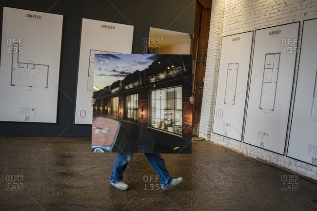 March 27, 2014: A man carries a picture at the opening of a new housing development in Toronto