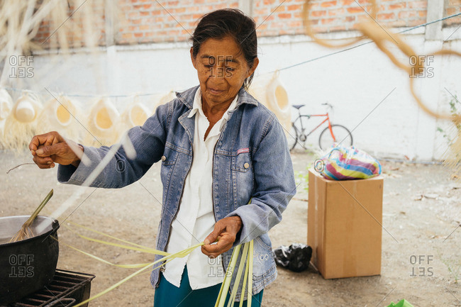 Manta, Ecuador - January 26, 2015: Craftswoman weaving a hat in Ecuador