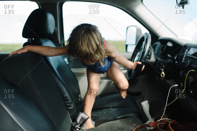 Little girl walking across a vehicle seat