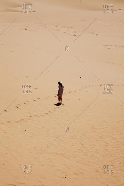 A young woman walks through a sandy desert