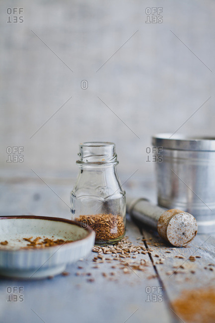 Jar of whole cumin seeds, pestle and dish for grinding into powder