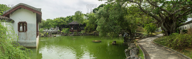 Okinawa, Japan - June 28, 2015: Visitors on bridge at Fukushu-en Garden pond in Okinawa, Japan