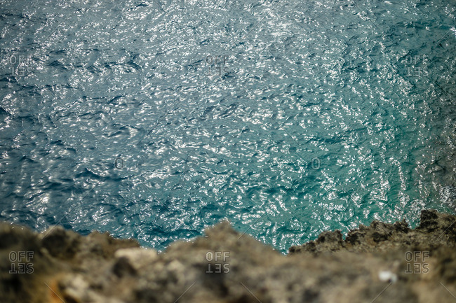 Looking down at blue water from volcanic rock cliff