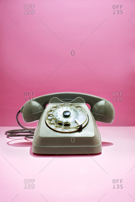 Rotary telephone in studio shot with pink background