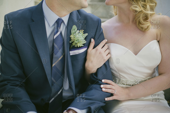 Seated portrait of groom and bride from neck down