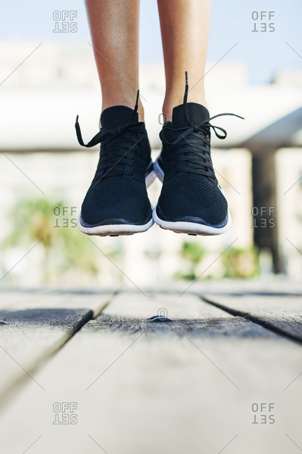 Sportive young woman wearing black sneakers jumping in the air