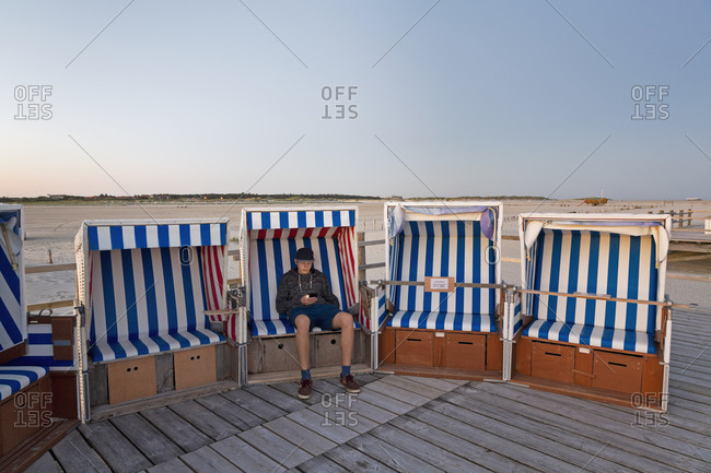 Teenage boy with smartphone sitting in hooded beach chair
