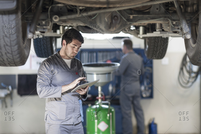 Car mechanic using digital tablet in repair garage