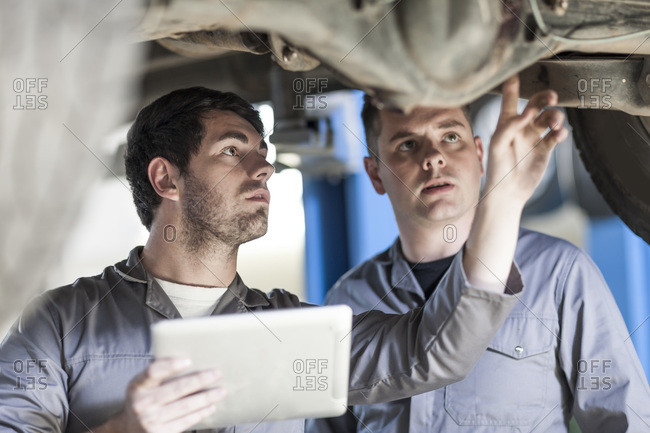 Two car mechanics at work in repair garage