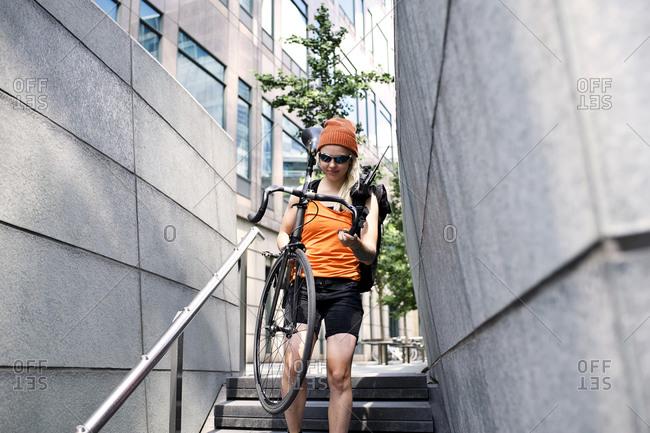 Woman carrying a bike down steps