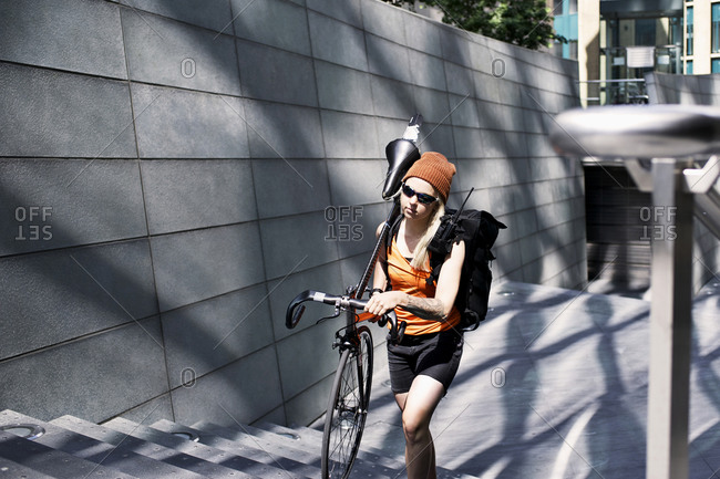 Woman carrying her bike up stairs