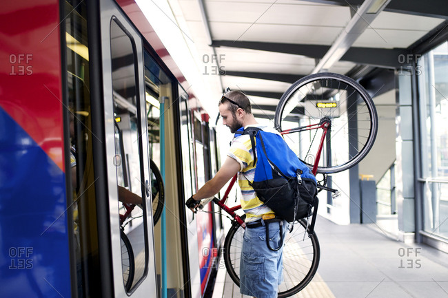 Man boarding subway train with his bicycle